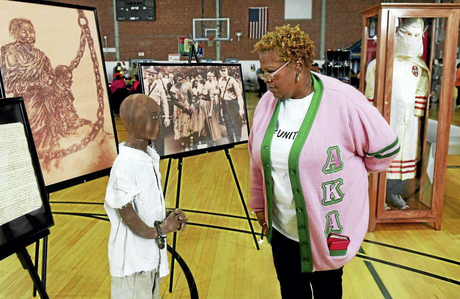"Volunteer Saron Jones McCann, a member of the Alpha Kappa Alpha sorority, examines an exhibit, ""The African American Collection: America's Distored Images,"" at the Martin Luther King Youth Conference at Wexler-Grant Community School Monday in New Haven. Photo: Peter Hvizdak — New Haven Register   / ©2016 Peter Hvizdak"