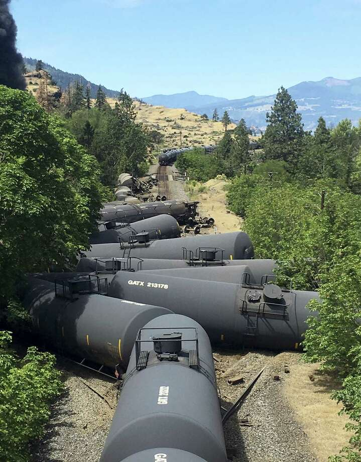 In this photo provided by Silas Bleakley, tank cars, carrying oil, are derailed Friday, June 3, 2016, near Mosier, Ore. The accident happened just after noon about 70 miles east of Portland. It involved numerous cars filled with oil, and one was burning. Highway 84 was closed for a 23-mile stretch between The Dalles and Mosier and the radius for evacuations was a half-mile. Photo: Silas Bleakley Via AP / Silas Bleakley