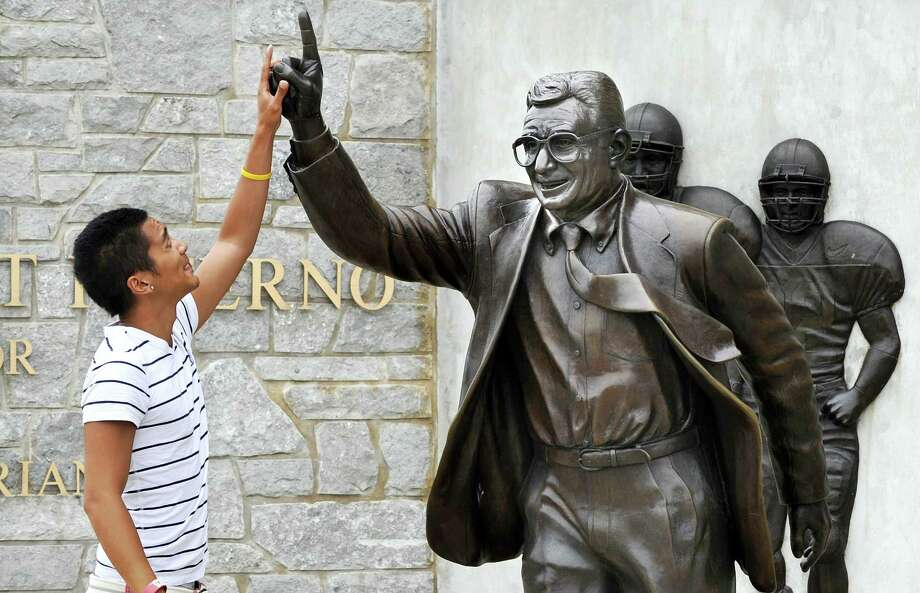 In this 2013 file photo, Joseph Jacobo, a senior at Penn State University, places his hand on the hand of the statue of Joe Paterno. Photo: YORK DAILY RECORD/SUNDAY NEWS — JASON PLOTKIN    / YORK DAILY RECORD/SUNDAY NEWS