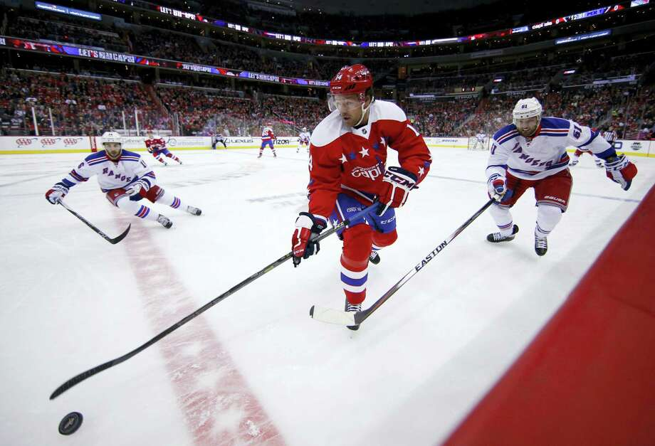 Washington Capitals right wing Justin Williams (14) skates with the puck with the Rangers' Derick Brassard and Rick Nash giving chase on Sunday. Williams had a hat trick and the Capitals won 5-2. Photo: The Associated Press   / AP