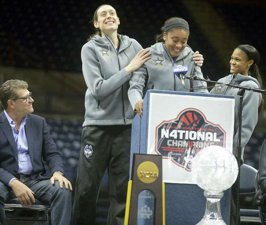 UConn's Breanna Stewart, left,  congratulates Morgan Tuck, center, as Moriah Jefferson, looks on, during a rally inside Gampel Pavilion Wednesday. Tuck was surprised with her induction into the Huskies of Honor. Photo: Jim Michaud — Journal Inquirer Via AP   / Journal Inquirer