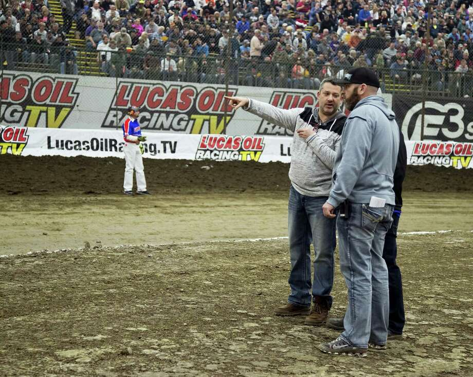 In this photo from Wednesday, NASCAR driver Tony Stewart gestures while talking about the track with Brad Chandler during Chili Bowl midget races at Tulsa's Expo Square in Tulsa, Okla. Police are investigating after an off-duty officer heckled Stewart and was confronted by the driver on Friday. Photo: The Associated Press File Photo   / For the Tulsa World
