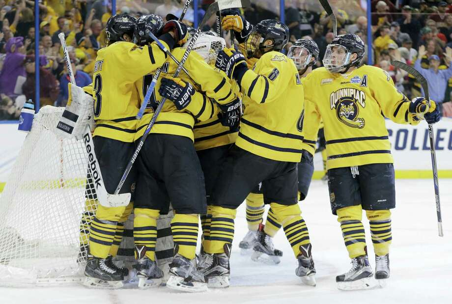 Quinnipiac players mob goalie Michael Garteig after the Bobcats beat Boston College 3-2 in a national semifinal on Thursday in Tampa, Fla. Photo: Chris O'Meara — The Associated Press   / AP