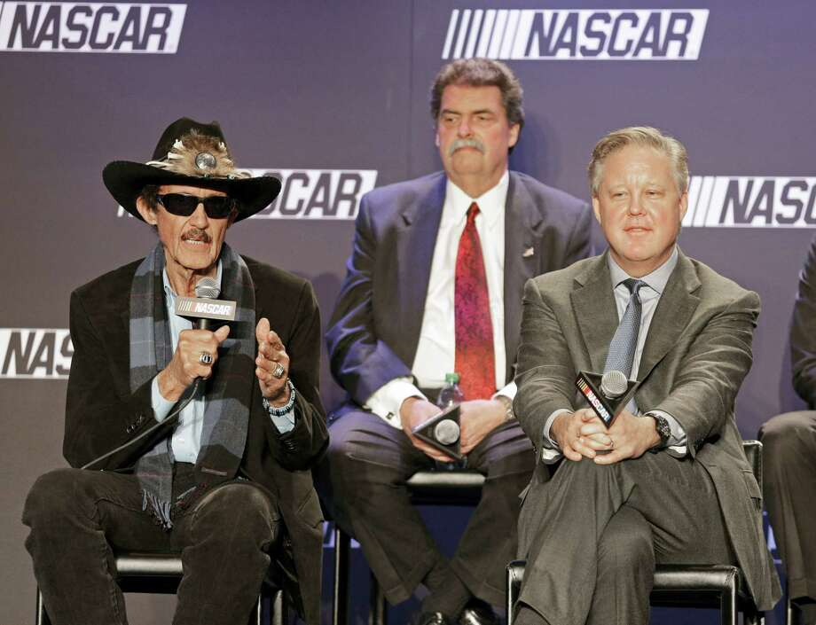 Team owner Richard Petty, left, speaks as NASCAR Chairman and CEO Brian France, right, and NASCAR president Mike Helton, back, listens during a news conference on Tuesday. Photo: Chuck Burton — The Associated Press    / AP