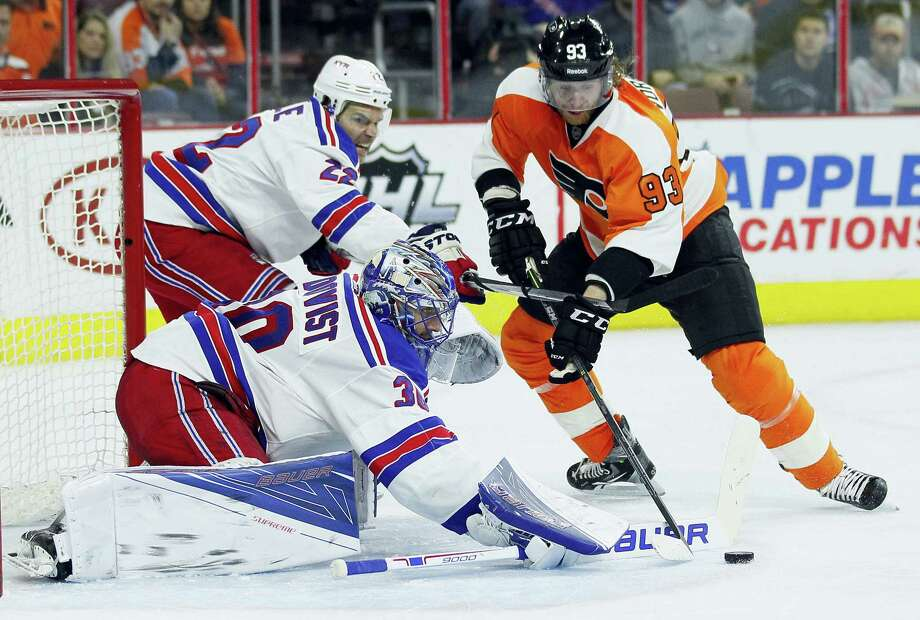 Rangers goalie Henrik Lundqvist, center, deflects the puck from the Flyers' Jakub Voracek in the second period on Sunday. Photo: Tom Mihalek — The Associated Press   / FR148949 AP