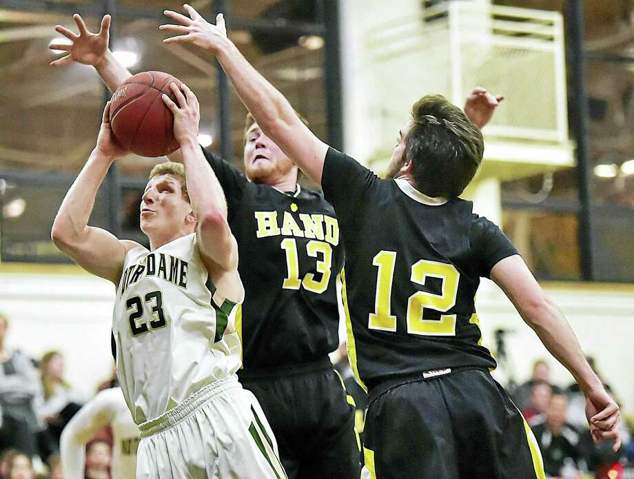 Notre Dame-West Haven freshman Connor Raines drives past Hand's Andrew Fitzgerald (12) to help the Green Knights defeat the Tigers of Madison, 70-62, in the second round of the CIAC class L boys basketball tournament Wednesday in West Haven. Photo: Catherine Avalone — New Haven Register   / New Haven RegisterThe Middletown Press
