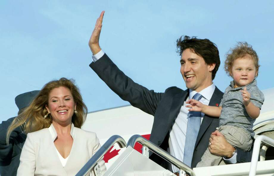 Prime Minister Justin Trudeau, holding his son Hadrian, waves as he steps off the plane with his wife Sophie Gregoire-Trudeau during a welcome ceremony at Andrews Air Force Base, Md., Wednesday, March 9, 2016. Photo: Paul Chiasson/The Canadian Press Via AP    / CP