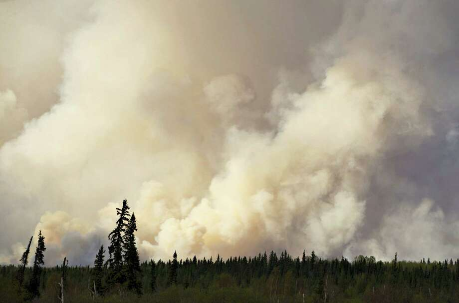 Smoke rises as a wildfire burns near Fort McMurray, Alberta, Thursday, May 5, 2016. An ever-changing, volatile situation is fraying the nerves of residents and officials alike as a massive wildfire continues to bear down on the Fort McMurray area of northern Alberta. The province of Alberta declared a state of emergency. Photo: Jason Franson — The Canadian Press Via AP / The Canadian Press