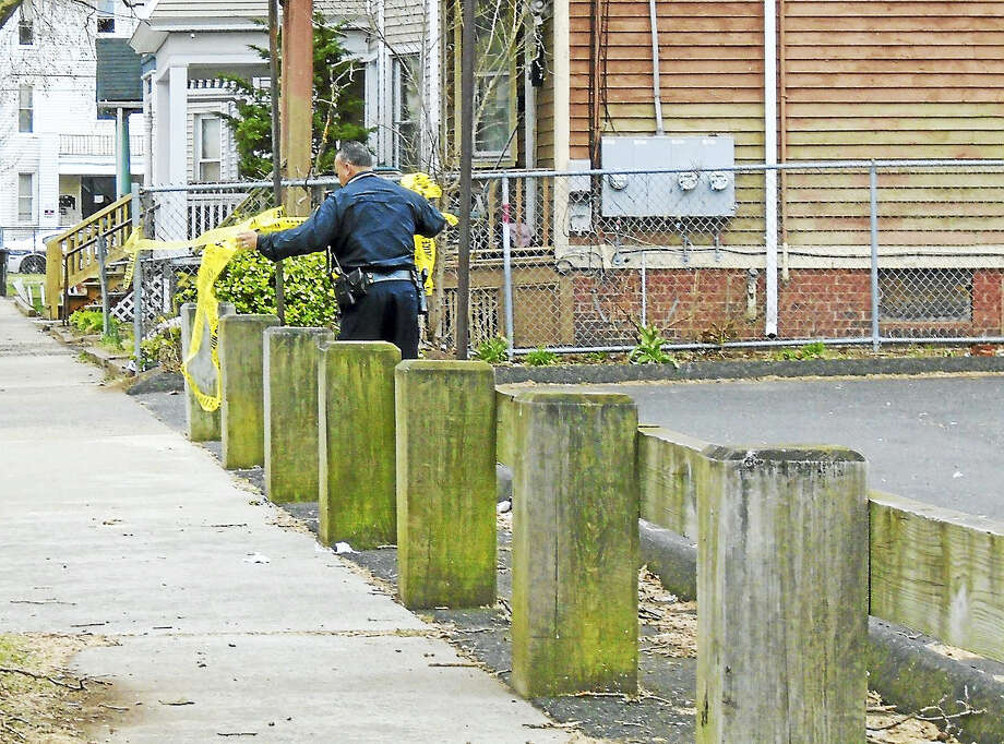 A New Haven police officer takes down crime scene tape Thursday morning on May Street near State Street. May Street was blocked for hours Thursday morning after a city man was found there with a gunshot wound to the head. Photo: Wes Duplantier — The New Haven Register   / Copyright 2009