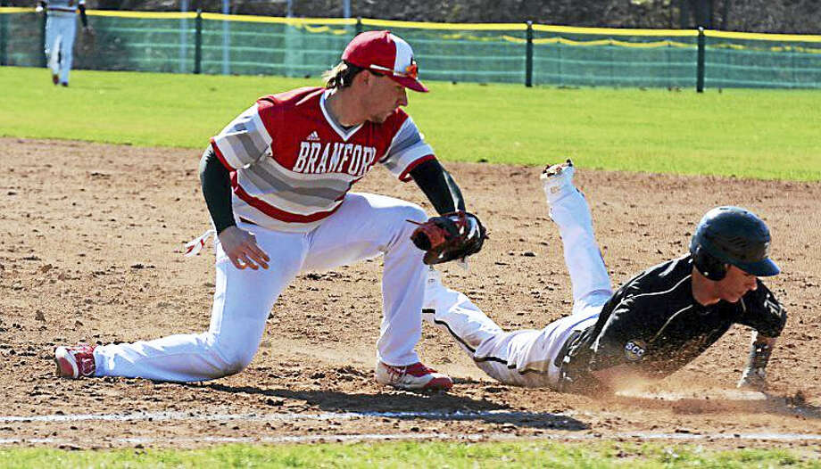 Law baserunner Frank Mucciacciaro slides back into first base safely as Branford first baseman Devin Derenzo looks on. Law beat Branford 9-2. Photo: Dave Phillips — GameTime CT