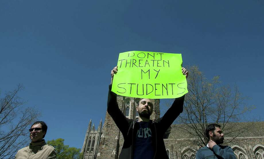 In this April 3, 2016 photo, Matteo Gilebbi, center, an Italian instructor at Duke University, holds a sign during a protest outside the Allen Building on campus in Durham, N.C. Duke University officials say student protesters are occupying the reception area near the school president's office for a fifth day. Photo: Kaitlin McKeown/The Herald-Sun Via AP   / The Herald-Sun