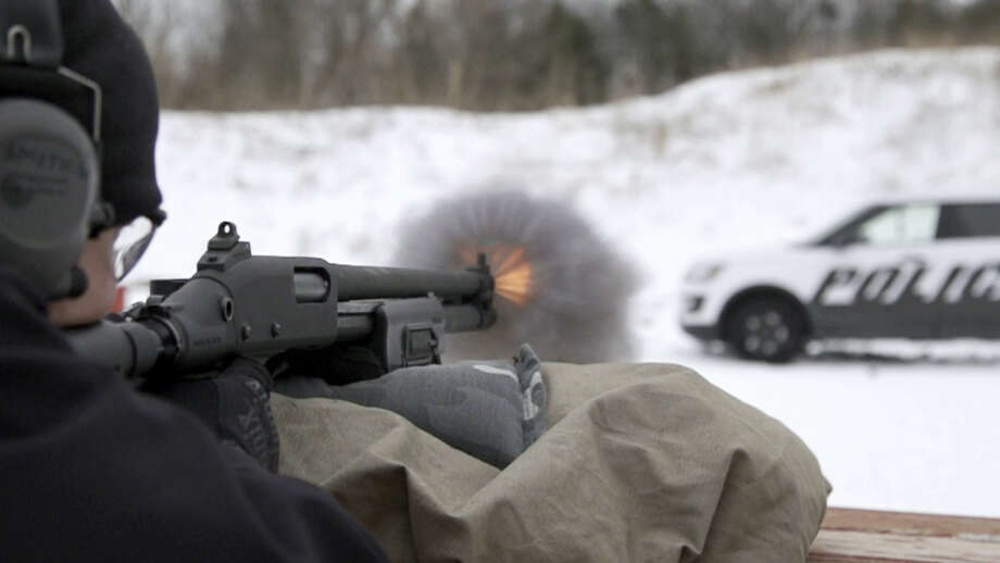 In this March 3, 2016, photo provided by Ford Motor Company, a Michigan State Police officer shoots at the doors of a Ford Police Interceptor Utility vehicle during ballistic testing of doors against small arm fire at the Livingston Conservation and Sports Association in Brighton, Mich. Ford will soon be offering doors on its Police Interceptor sedans and SUVs that can protect against armor-piercing bullets. They'll be the first in the U.S. to meet the Justice Department's highest standard for body armor, the equivalent of a bulky SWAT team vest. Photo: Ryan Koehler/Ford Motor Company Via AP   / Ford Motor Company
