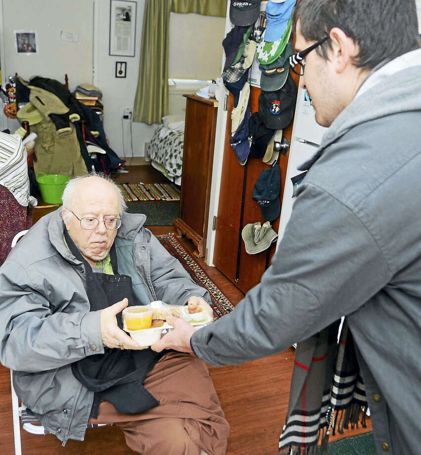 Larry Killian receives a meal from a SARAH volunteer. Photo: Photos By Kelly Quinlan Goddard