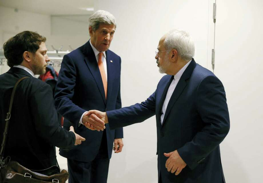 U.S. Secretary of State John Kerry shakes hands with Iranian Foreign Minister Mohammad Javad Zarif, right, after the International Atomic Energy Agency (IAEA) verified that Iran has met all conditions under the nuclear deal, in Vienna, Austria, Saturday Jan. 16,  2016. U.S. Secretary of State, John Kerry confirms Iran in compliance with nuclear deal and lifts US nuclear-related sanctions. Photo: Kevin Lamarque/Pool Via AP / Reuters Pool