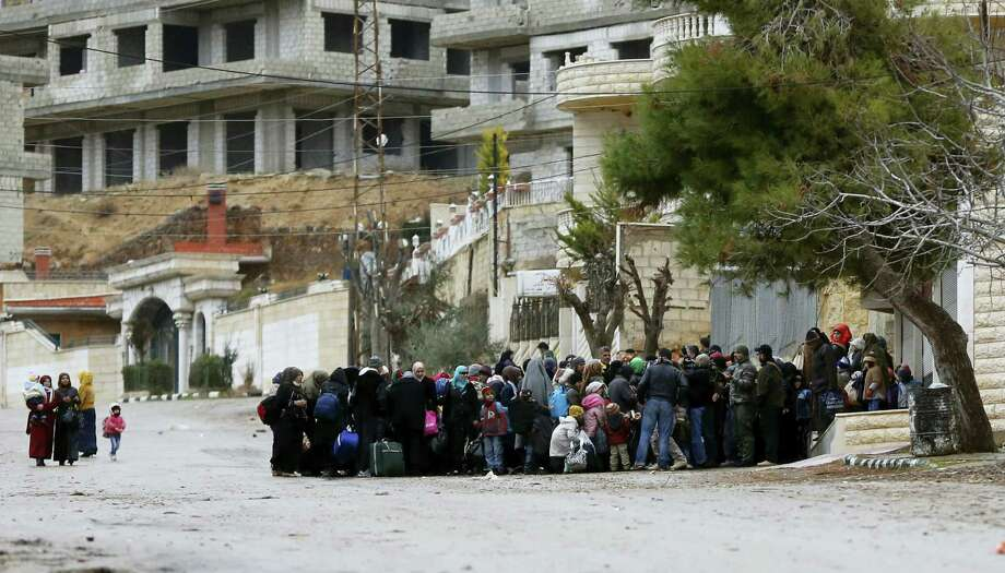 Syrians wait for an aid convoy in the besieged town of Madaya in the countryside of Damascus, Syria, on Thursday as part of a UN-sponsored aid operation in this war-torn country. Photo: ASSOCIATED PRESS   / AP