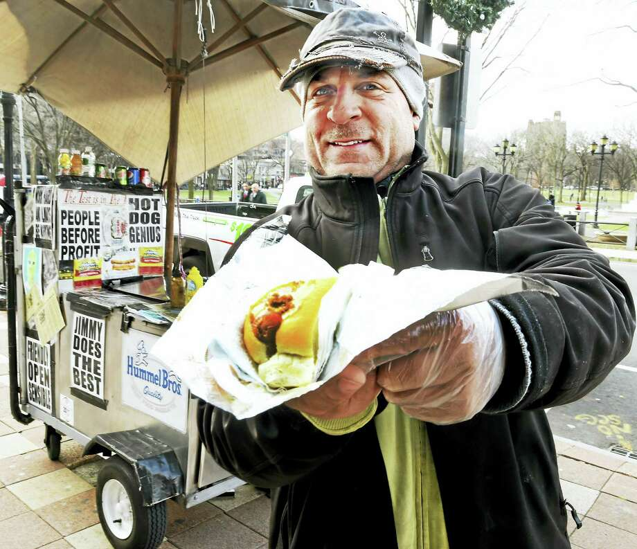 Jimmy Nigretti, all bundled up for a winter's day of work, shows off one of his hot dogs. Photo: PETER HVIZDAK — NEW HAVEN REGISTER   / ?2016 Peter Hvizdak