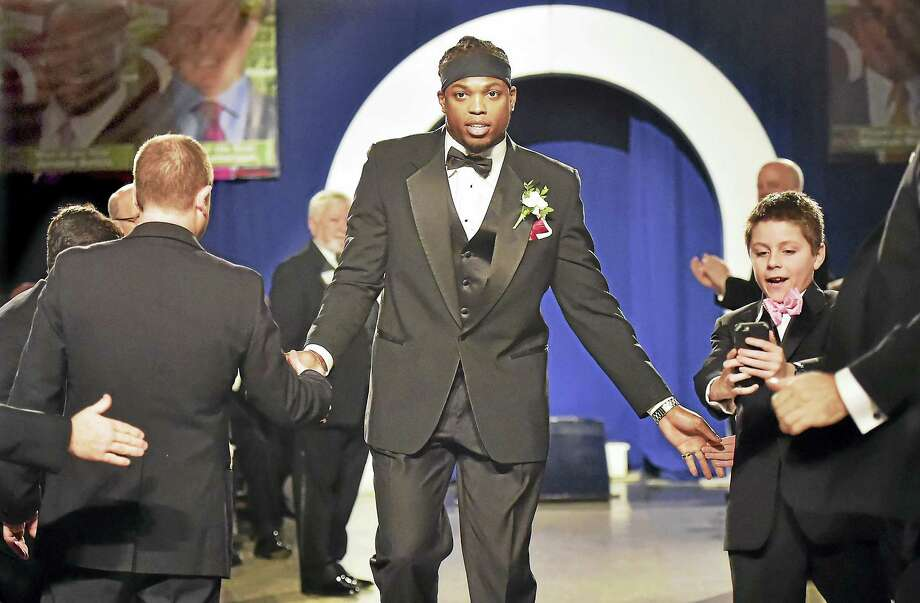 (Catherine Avalone - New Haven Register)   Sam Anastasio, 11, 0f Woodbridge snaps a picture of the 2015 Walter Camp Football Foundation Player of the Year, Derrick Henry, as he is announced at the 49th annual awards dinner, Saturday, January 16, 2016, at Yale University Commons. Henry, a junior running back at University of Alabama leads the nation in rushing, 2,061 yards to set both school and SEC single-season records, was voted by the nation's 129 FBS head coaches and sports information directors.. Henry beat out finalists, Stanford's Christian McCaffrey, Oklahoma quarterback, Baker Mayfield, Clemson QB Deshaun Watson and  Iowa defensive back Desmon King. Photo: Journal Register Co. / New Haven RegisterThe Middletown Press