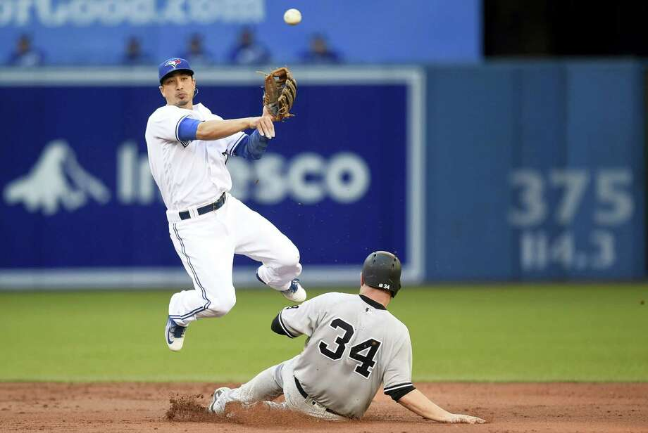 New York Yankees' Brian McCann is out at second as Toronto Blue Jays' Darwin Barney throws to first during the second inning in Toronto, Wednesday. Yankees' Mark Teixeira grounded into fielder's choice and was safe at first on the play. Photo: FRANK GUNN — THE CANADIAN PRESS VIA AP   / CP