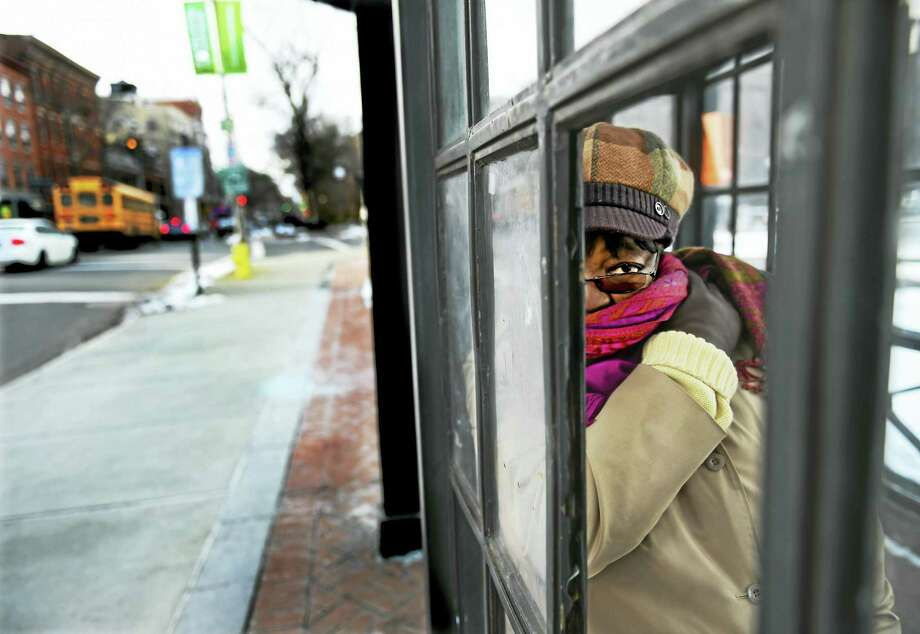 Gladys Brown of New Haven huddles in an enclosed bus stop Thursday afternoon on Chapel Street in New Haven as she waits for her bus to arrive. Photo: Peter Hvizdak — New Haven Register   / ©2016 Peter Hvizdak
