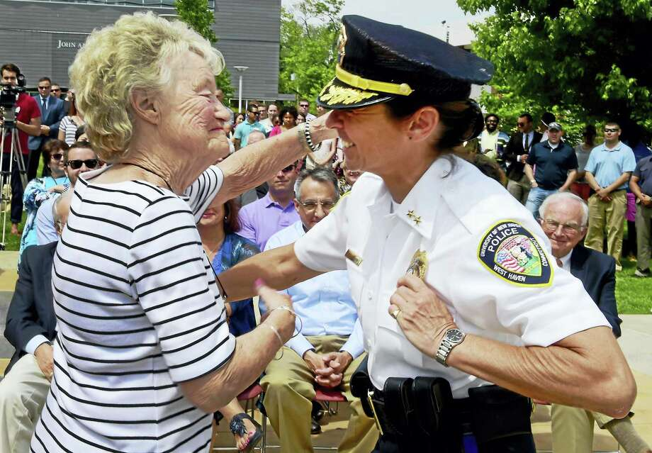 Florence Mooney, left, congratulates her daughter, new University of New Haven Police Chief Tracy L. Mooney, after pinning on her badge during a swearing-in ceremony Wednesday at UNH. Photo: Peter Hvizdak — New Haven Register   / ©2016 Peter Hvizdak