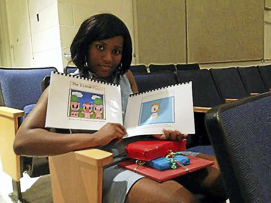 Quiana Copeland, a senior at James Hillhouse High School, poses with two of her books and her awards. Photo: Brian Zahn — New Haven Register