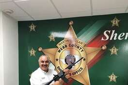 Sheriff Martin Cuellar poses with two rifles awarded by the NRA to the Webb County Sheriff's Office.