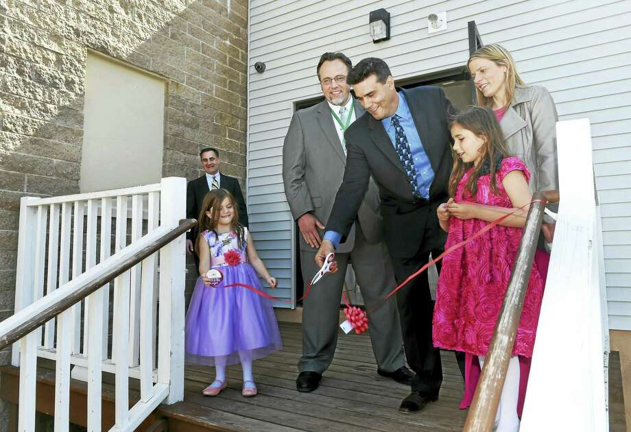 Attorney Bernie Pelligrino, far left, watches Sienna Natale, 5, Hamden Mayor Curt Leng, developer Joseph Natale, his other daughter, Miley Natale, 7, and his wife, Stacey Natale, during a ribbon-cutting ceremony that officially opened his Millstone Apartment building at 383 Putnam Ave. in Hamden. Photo: Peter Hvizdak — New Haven Register   / ©2016 Peter Hvizdak