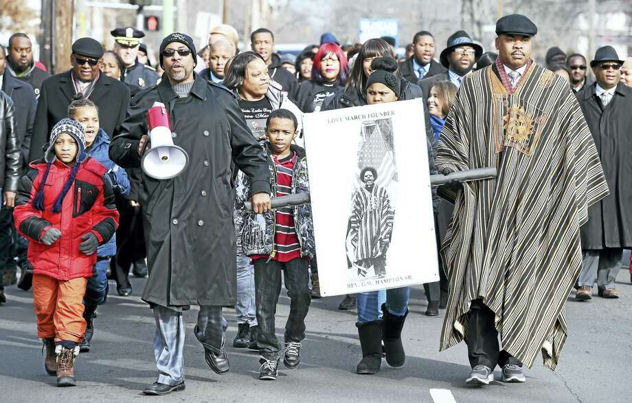 The Rev. Kennedy Hampton Sr., left, and his brother, the Rev. Gerald Hampton, right, carry a picture of their late father, the Rev. George W. Hampton Sr. during the Shiloh Missionary Baptist Church's annual Love March Friday in New Haven. Photo: Arnold Gold — New Haven Register