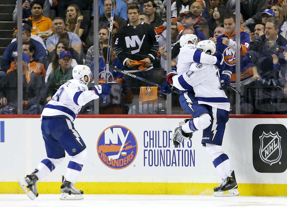 Tampa Bay Lightning right wing Ryan Callahan, center, jumps into the arms of center Brian Boyle (11) as Tampa Bay Lightning center Cedric Paquette (13) rushes in after Boyle scored the game-winning goal against the New York Islanders during the overtime period of Game 3 of the NHL hockey Stanley Cup Eastern Conference semifinals Tuesday in New York. The Lightning won 5-4. Photo: FRANK FRANKLIN III — THE ASSOCIATED PRESS   / Copyright 2016 The Associated Press. All rights reserved. This material may not be published, broadcast, rewritten or redistribu