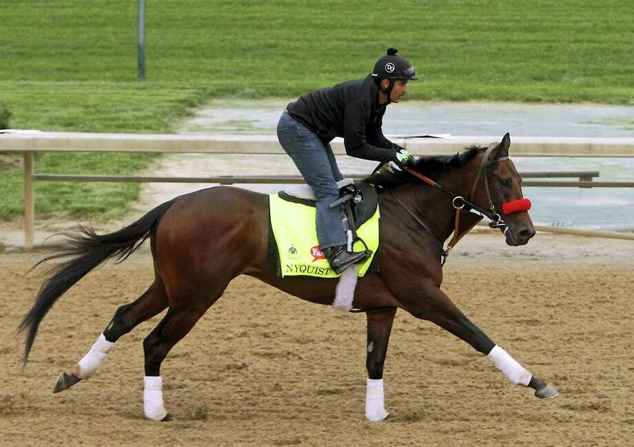 Kentucky Derby hopeful Nyquist, ridden by Jonny Garcia, gallops at Churchill Downs. Nyquist is a 3-1 favorite for Saturday's 142nd running of the Kentucky Derby. Photo: Gary Jones — The Associated Press   / FR50389 AP