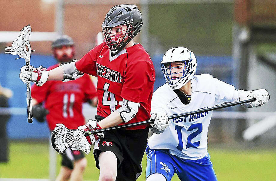 Cheshire senior attack Griffin Cunningham battles West Haven junior defenseman Sergio Miranda in a, 17-2, win Tuesday for the Rams at Ken Strong Stadium at West Haven High School. Photo: Catherine Avalone — New Haven Register   / New Haven RegisterThe Middletown Press
