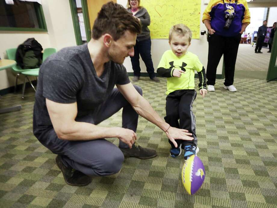 Max Birdwell, 4, kicks a football from the hold of Vikings kicker Blair Walsh during a visit to Northpoint Elementary School, Thursday in Blaine, Minn. First graders at the school wrote letters of encouragement to Walsh after he missed a potentially game-winning field goal in last Sunday's NFL football playoff game against the Seahawks. Photo: Jerry Holt — Star Tribune Via AP   / Star Tribune