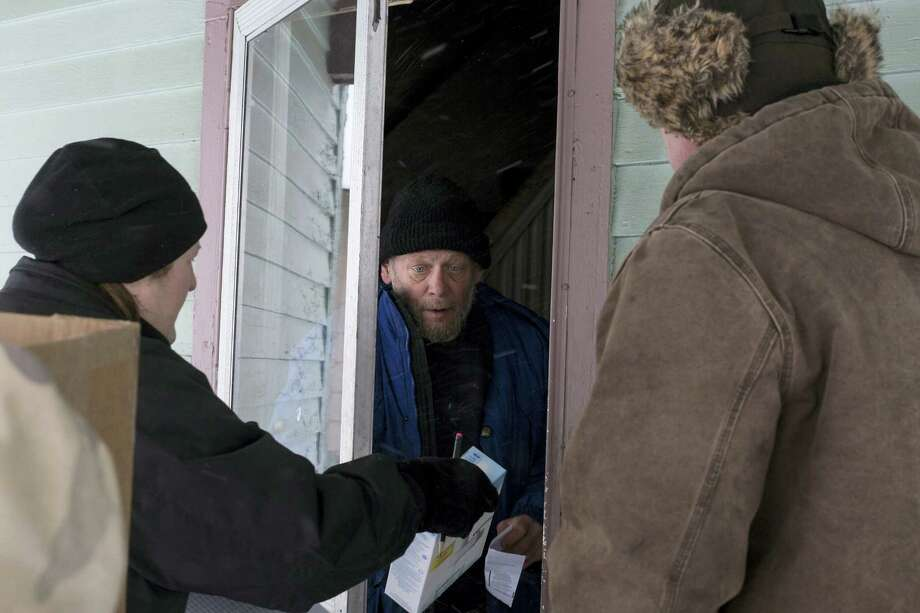 Volunteers go door to door in Flint Neighborhoods distributing water filters, replacement cartridges, and bottled water on Tuesday, Jan. 12, 2016. The volunteers were escorted by State Police and Genesee Country Sheriff's deputies. Safe drinking water has not flowed from many Flint faucets for almost two years after the state-run city switched its source to the highly corrosive Flint River and failed to treat it properly to protect lead from leaching into it. Photo: Conor Ralph/The Flint Journal-MLive.com Via AP    / The Flint Journal