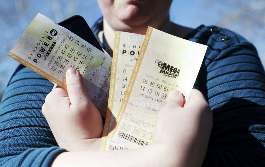 "Stephanie Barnett, of Center Point, Ala., holds up Powerball lottery tickets at Georgia Visitor Information Center, Wednesday, Jan. 13, 2016, in Tallapoosa, Ga. ""If I win, I want to build a new house,"" says Barnett. Photo: AP Photo/Brynn Anderson    / AP"