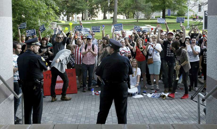 Protesters gather outside the North Carolina Museum of History as Gov. Pat McCrory make remarks about House Bill 2 during a government affairs conference in Raleigh, N.C., Wednesday, May 4, 2016. A North Carolina law limiting protections to LGBT people violates federal civil rights laws and can't be enforced, the U.S. Justice Department said Wednesday, putting the state on notice that it is in danger of being sued and losing hundreds of millions of dollars in federal funding. Photo: AP Photo — Gerry Broome / Copyright 2016 The Associated Press. All rights reserved. This material may not be published, broadcast, rewritten or redistribu