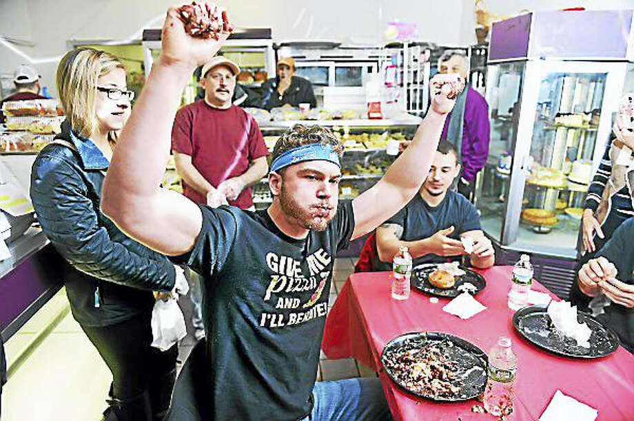 "Arnold Gold — New Haven Register  Brandon ""Feast Mode"" Carr rejoices after winning the annual paczki-eating contest at Eddy's Bake Shop in Ansonia. Photo: Journal Register Co."