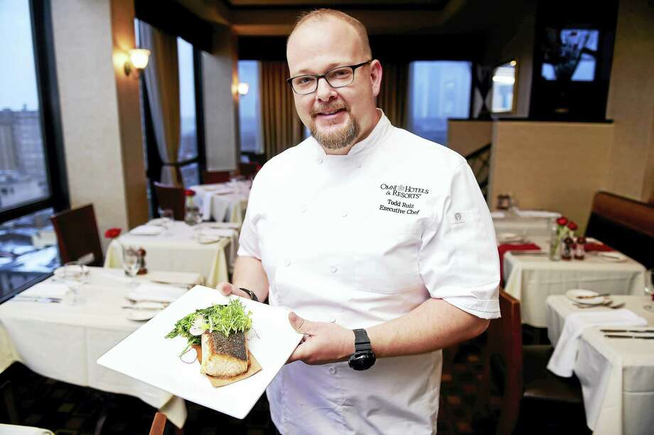 Executive Chef Todd Ruiz of John Davenport's at the Top of the Park is photographed with cedar plank salmon with garlic spinach topped with a frisee and radish salad. Photo: Arnold Gold — New Haven Register