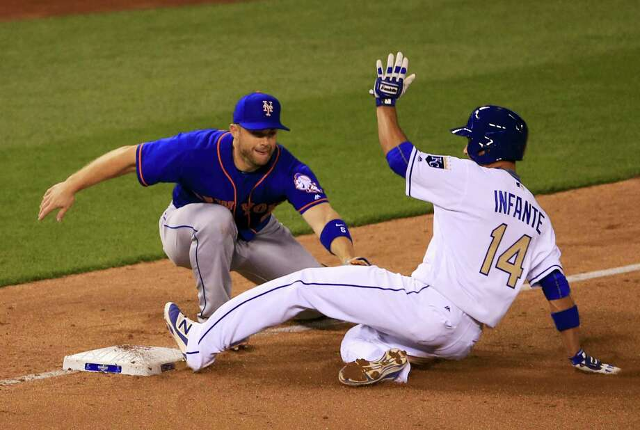 Kansas City Royals' Omar Infante, right, beats the tag by New York Mets third baseman David Wright, left, during the fifth inning of a baseball game at Kauffman Stadium in Kansas City, Mo., Sunday, April 3, 2016. (AP Photo/Orlin Wagner) Photo: AP / Copyright 2016 The Associated Press. All rights reserved. This material may not be published, broadcast, rewritten or redistributed without permission.