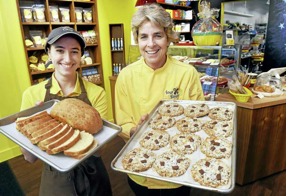 Assistant baker Morgan Metzler, left, holds rosemary shallot bread while Robin Schaffer, owner and chief baking officer of Four Flours Baking Company, holds oatmeal chocolate coconut cookies at Schaffer's store on Chapel Street in New Haven. Photo: Arnold Gold — New Haven Register