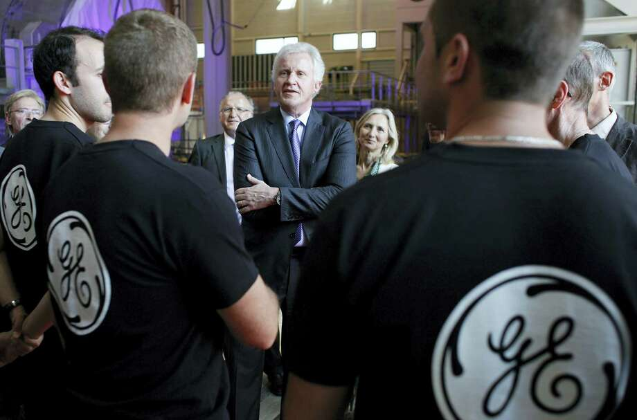 In this June 24, 2014 photo, General Electric Co. CEO Jeffrey R. Immelt, center, speaks with workers as he visits the General Electric plant in Belfort, eastern France. Photo: AP Photo/Thibault Camus, File   / AP