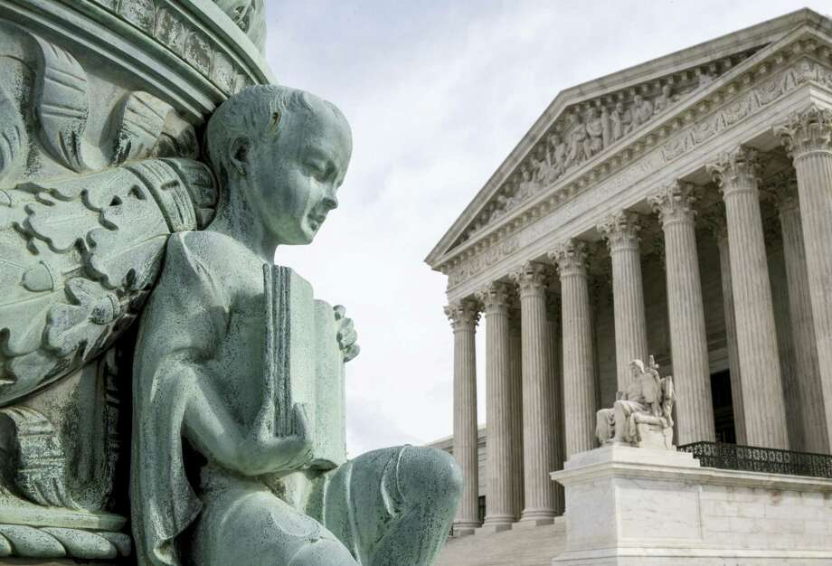 """A cherub holding an open book adorns a flagpole on the plaza of the Supreme Court in Washington on April 4, 2016. The justices ruled today in a case involving the constitutional principle of """"one person, one vote"""" and unanimously upheld a Texas law that counts everyone, not just eligible voters, in deciding how to draw legislative districts. Photo: AP Photo/J. Scott Applewhite   / AP"""