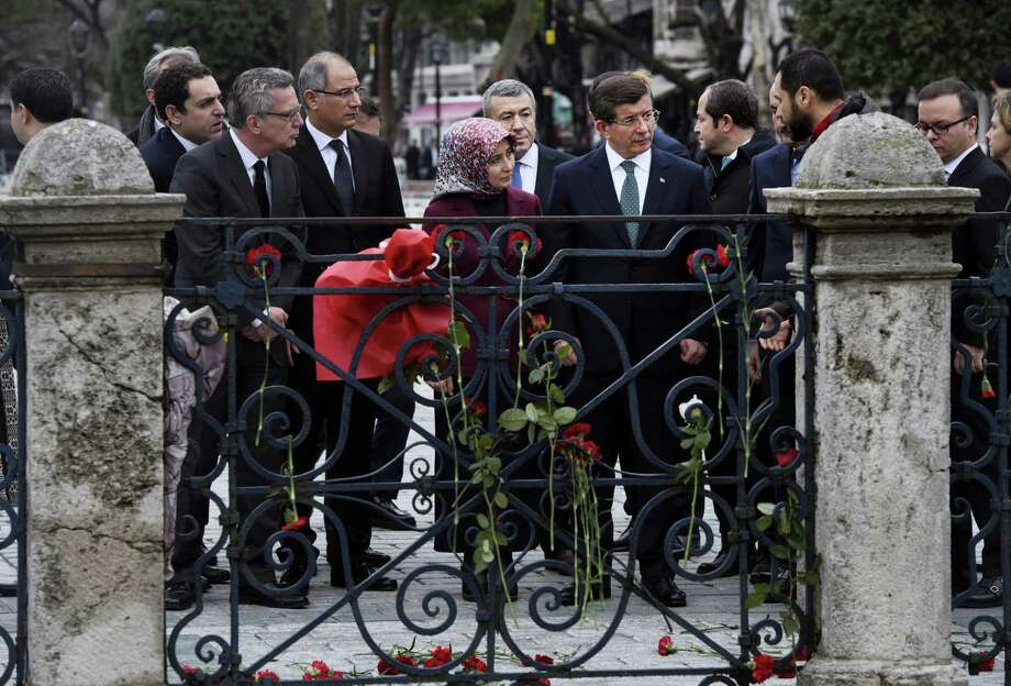 Turkey's Prime Minister Ahmet Davutoglu, centre right, accompanied by his wife Sare, centre and German Interior Minister Thomas de Maiziere, left, listen to a police officer talking to them about the attack, during a visit at the site of Tuesday's explosion, in the historic Sultanahmet district of Istanbul, Wednesday, Jan. 13, 2016. A suicide bomber detonated a bomb in the heart of Istanbul's historic district on Tuesday, killing a number of German tourists and wounding over a dozen others, in the latest in a string of attacks by the Islamic extremists targeting westerners. Photo: Bulent Kilic, Pool Photo Via AP    / POOL