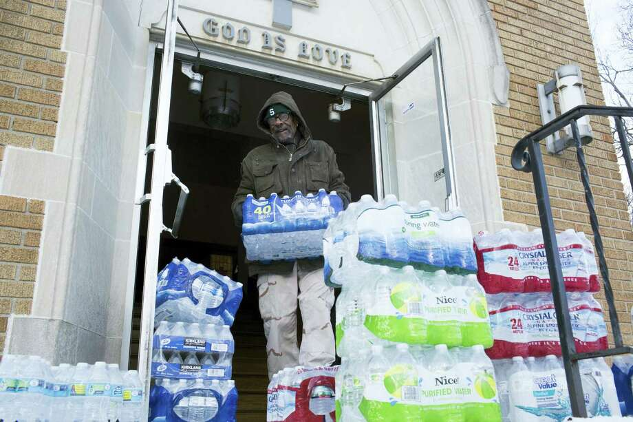 Maurice Rice organizes cases of water at the Joy Tabernacle Church on Monday, Jan. 11, 2016, in Flint, Mich. Michigan Gov. Rick Snyder pledged Monday that officials would make contact with every household in Flint to check whether residents have bottled water and a filter and want to be tested for lead exposure while his embattled administration works on a long-term solution to the city's water crisis. Photo: Conor Ralph/The Flint Journal-MLive.com Via AP    / The Flint Journal