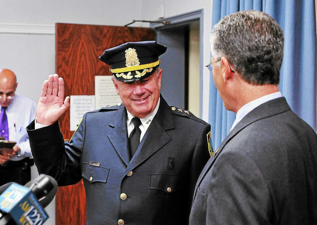 East Haven mayor Joseph Maturo Jr. swears in Brent Larrabee as the town's permanent police chief in a June 2013 ceremony at the Hagaman Memorial Library.