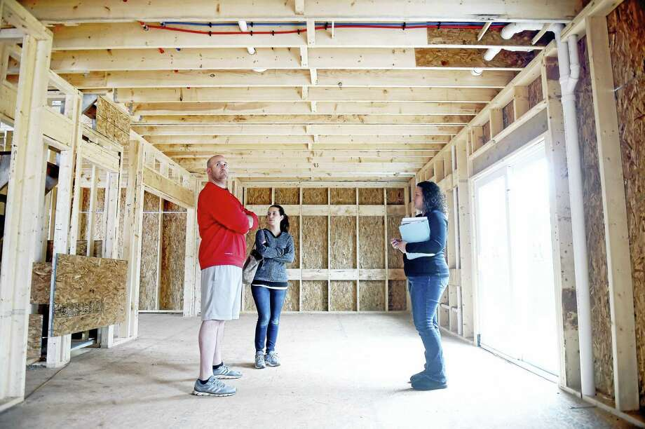 From left, David Crocco and his wife, Christina Crocco, talk with Sunwood Development Sales Coordinator Amy Standish inside their house under construction at the Royal Oaks development in Wallingford Friday, April 1, 2016. Growth in housing permits for the region in February of this year is up by 30 percent over last year. Photo: Arnold Gold — New Haven Register
