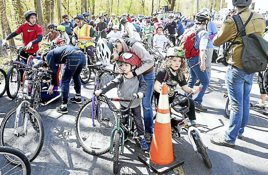 Leslie Frame (center) of New Haven secures a Spiderman helmet on her son, Sam Werlin, 6, at the start of the 8-mile ride in the 8th Annual Rock to Rock Earth Day Ride this weekend at West Rock Park in New Haven. Photo: Photo By Arnold Gold — New Haven Register