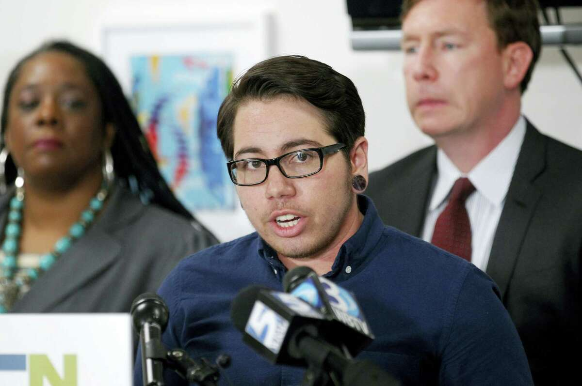 Joaquin Carcano, center, the lead plaintiff in the case, speaks during a press conference to announce the filing of a federal lawsuit challenging North Carolina's HB 2 law at the LGBT Center of Raleigh, N.C., on March 28, 2016. Joaquin was born female and is now a man. Simone Bell with Lambda Law is at left; Chris Brook with the ACLU is at right.