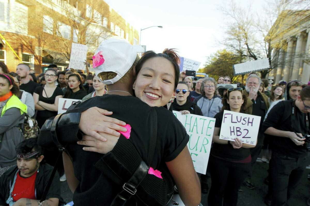 Protester Mitch Xia, center, facing camera, gets a hug from Zakyree Wallace, left, after speaking to the crowd in Chapel Hill, N.C. on March 29, 2016 to protest the recent passage of N.C. HB2. Republican Gov. Pat McCrory, seeking re-election in what's anticipated to be one of the nation's most heated and expensive campaigns, is doubling down on a sweeping law he signed last week preventing local governments from protecting people on the basis of sexual orientation and gender identity when they use public accommodations such as hotels and restaurants.