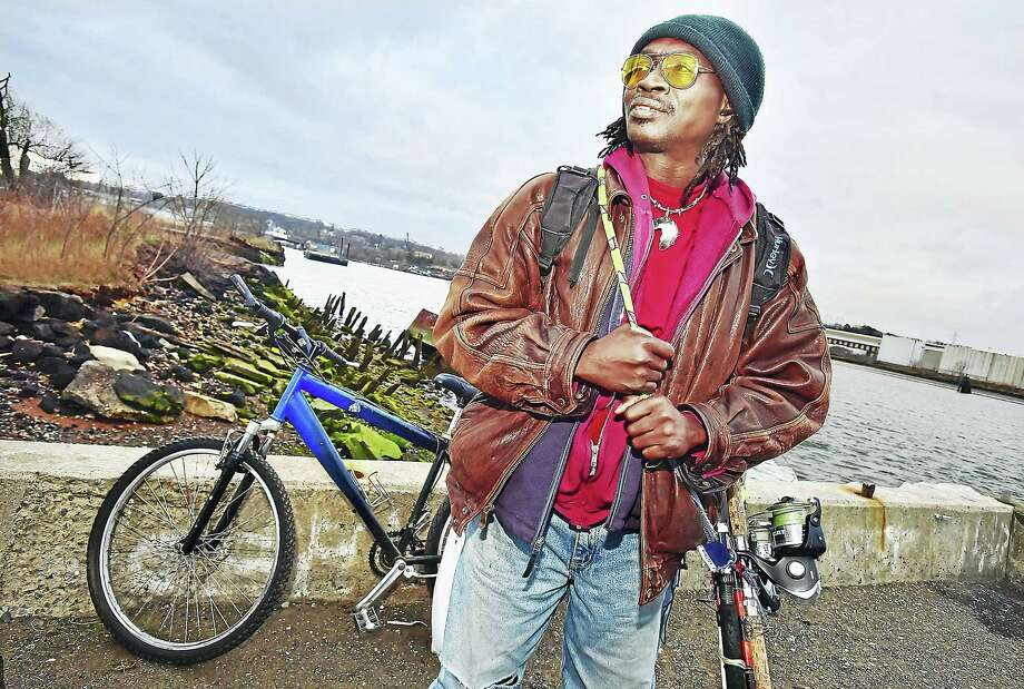 Aly Toatchol Camara of New Haven arrives at Criscuolo Park in New Haven to fish where the Quinnipiac and Mill rivers meet. Camara said that when the weather is warmer, the edge of the park is full of fishermen. He said he mostly fishes for sport, catching and releasing them. Photo: Catherine Avalone — New Haven Register   / New Haven RegisterThe Middletown Press