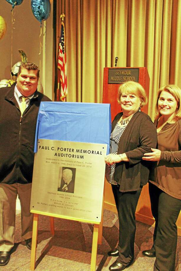 From left: Paul C. Porter's son Ryan Porter, wife Susan Porter, and daughter Cassie McLaughlin unveil the silver plaque dedicated in his honor. Photo: Jean Falbo-Sosnovich/New Haven Register